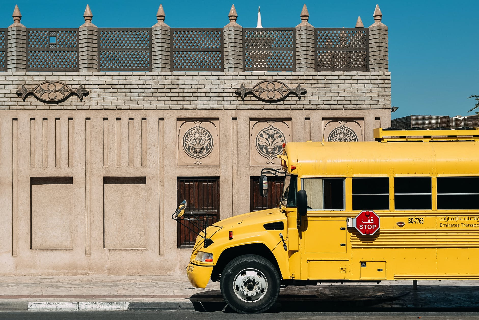 yellow school bus on route against historic building